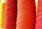 rolls of wool stood next to each other in shades of red and orange